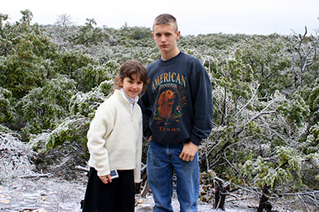 Sam and Mary in front of an icy canopy of tree tops