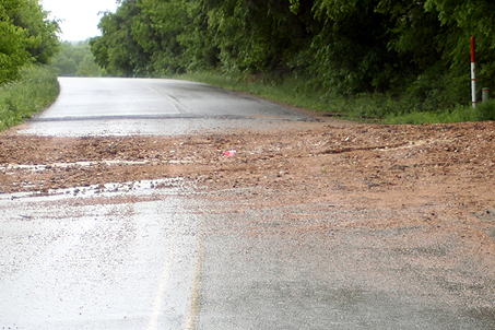 A dirt road is dragged by running water onto an intersecting road